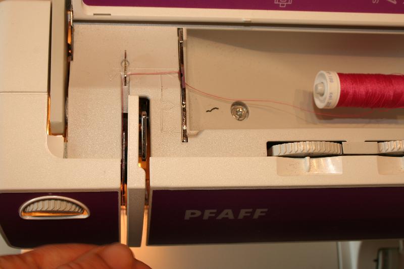Passage du fil par le guide-fil de la machine à coudre.