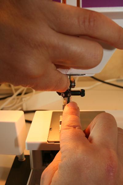 Passage du fil dans le guide-fil aiguille